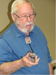 Don Monroe describes an item during a club auction.